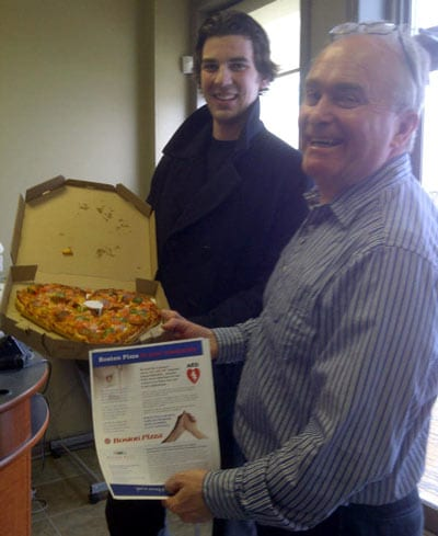Jordan Ryan from Boston Pizza delivers a complimentary heart shaped pizza to Terry Matchett at Mighty Miramichi
