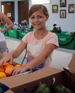 A young volunteer helps sort produce. (Photo by Annie Simoneau).