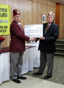 Noble Dave Bucklow, president of the Miramichi Shrine Club and Llewellyn Smith P.P., present a cheque for $1400 for Shriners Hospitals for Children.