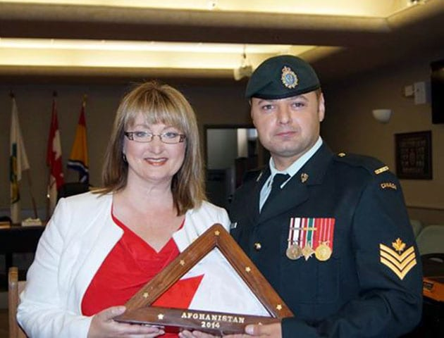 Brenda is presented with the final Canadian flag to fly over Camp Phoenix in Kabul, Afghanistan by Sgt. Martin Veilleux, a soldier who had received a shoe box.