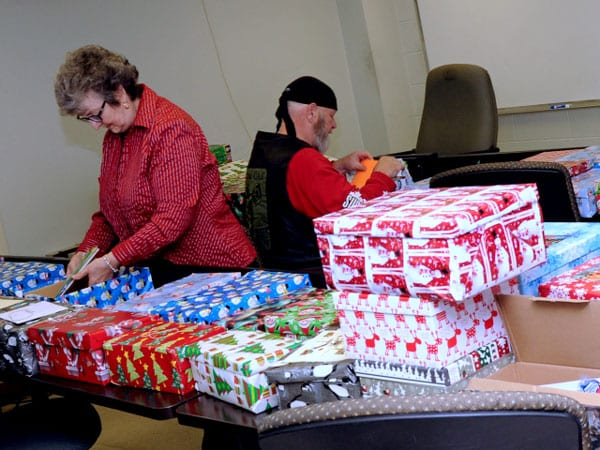 Brenda's mom, Elaine Dickson and Veteran Reg Pollock prepare shoeboxes for shipping.