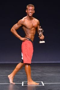 Adam Hambrook, owner of Sculpt Health & Fitness Miramichi being awarded NB Provincial Champion 2015 Men's Physique Short.
