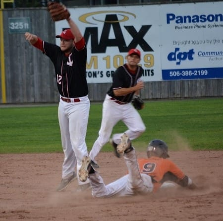 Spencer Stokes #9 steals second base as Tyler McKay leaps for the ball. Backing up the play is Gary Ryder as the Ironmen won 6-1 on Tuesday night. Photo by Brian Richard.